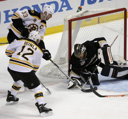 Anaheim Ducks goalie Jonas Hiller, right, blocks a shot by Boston Bruins defenseman Zdeno Chara (33) and right wing Jarome Iginla (12) during the first period of an NHL hockey game in Anaheim, Calif., Tuesday, Jan. 7, 2014. (AP Photo/Chris Carlson)