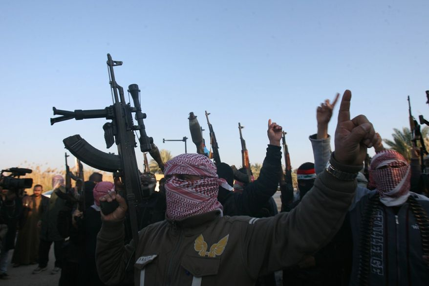 Gunmen gather in a street as they chant slogans against Iraq's Shiite-led government and demanding that the Iraqi army not try to enter Fallujah. U.S. intelligence analysts said al Qaeda's takeover of two Iraqi cities in Anbar province is an outgrowth of a jailbreak orchestrated last summer by the terrorist network. (Associated Press)