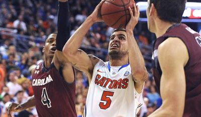 Florida guard Scottie Wilbekin (5) tries to get past South Carolina guard Tyrone Johnson (4) during the first half of an NCAA college basketball game Wednesday, Jan. 8, 2014 in Gainesville, Fla. (AP Photo/Phil Sandlin)