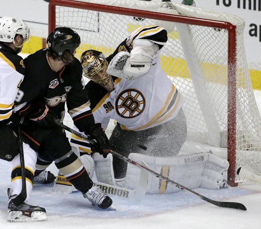 Boston Bruins goalie Tuukka Rask, right, blocks shot by Anaheim Ducks left wing Matt Beleskey during the first period of an NHL hockey game in Anaheim, Calif., Tuesday, Jan. 7, 2014. (AP Photo/Chris Carlson)