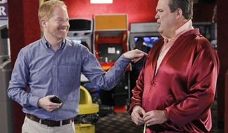 """This TV publicity image released by ABC shows Eric Stonestreet, as Cameron, right, and Jesse Tyler Ferguson as Mitchell in a scene from the comedy """"Modern Family.""""  Qantas airline is partnering with the show's production company, 20th Century Fox, to fly the cast to Australia next month for a two week shoot of an upcoming vacation episode of the ABC comedy. The comedy, now in its fifth season, has aired previous vacation episodes that were filmed in Hawaii and Wyoming. (AP Photo/ABC, Peter """"Hopper"""" Stone)"""