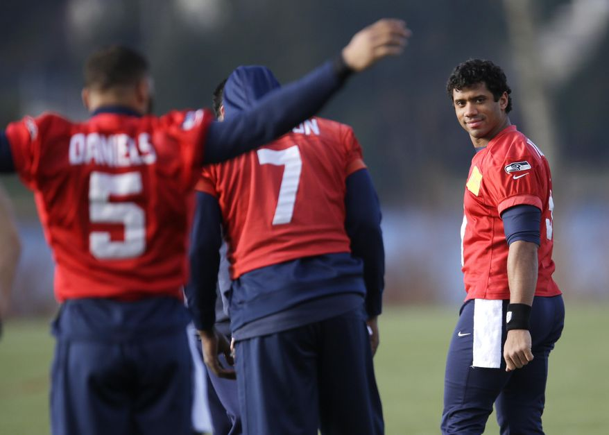 Seattle Seahawks quarterback Russell Wilson, right, looks toward his teammates as he stretches with practice squad quarterback B.J. Daniels (5) and backup quarterback Tarvaris Jackson (7) before NFL football practice, Friday, Jan. 3, 2014, in Renton, Wash. Seattle plays at home in a playoff game on Jan. 11. (AP Photo/Ted S. Warren)