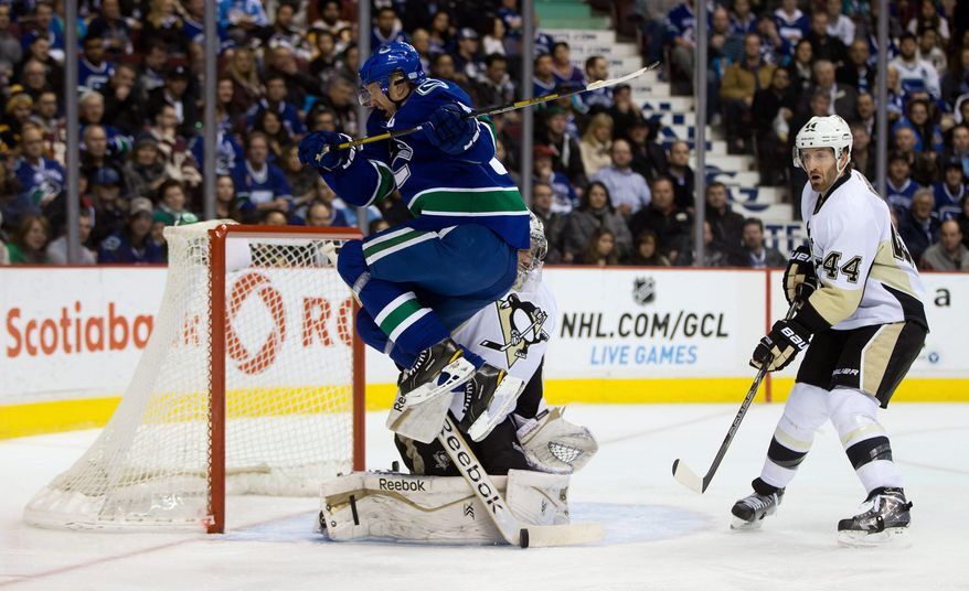 Vancouver Canucks' Henrik Sedin, left, of Sweden, jumps as Pittsburgh Penguins' Marc-Andre Fleury, center, makes the save while Brooks Orpik, right, watches during the first period of an NHL hockey game Tuesday, Jan. 7, 2014, in Vancouver, British Columbia. (AP Photo/The Canadian Press, Darryl Dyck)