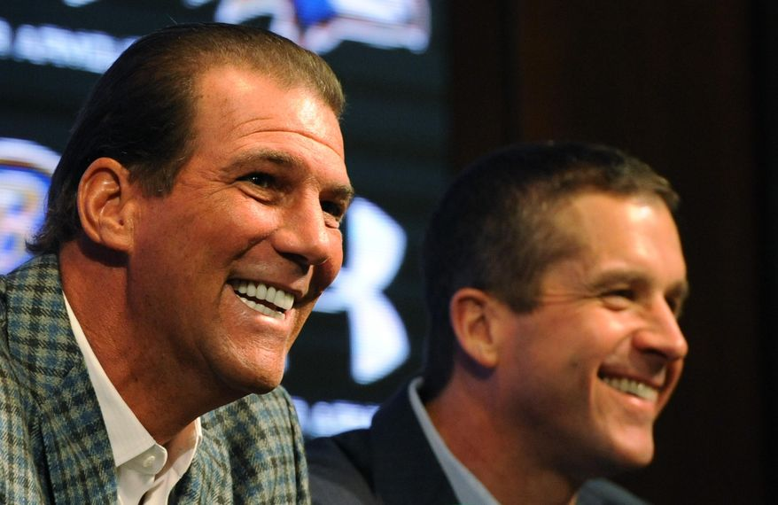 Baltimore Raven's owner Steve Bisciotti, left, and head coach John Harbaugh smile during a news conference Wednesday, Jan 8, 2014 in Owings Mills, Md.(AP Photo/Gail Burton)