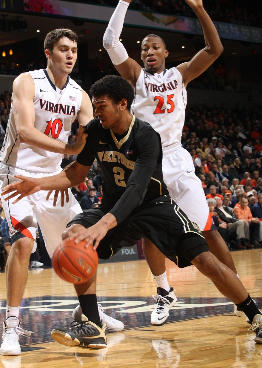 Wake Forest forward Devin Thomas (2) is defended by Virginia's Mike Tobey (10) and forward Akil Mitchell (25) during the first half of an NCAA college basketball game Wednesday, Jan. 8, 2014, in Charlottesville, Va. (AP Photo/Andrew Shurtleff)
