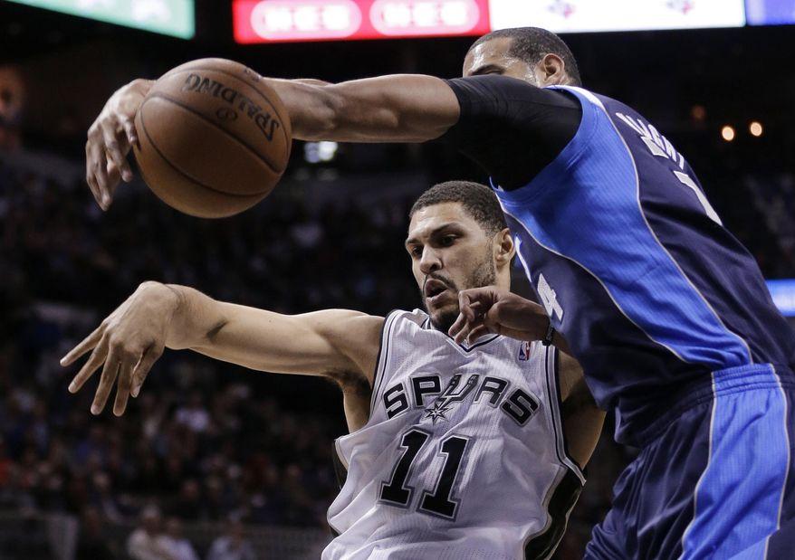 Dallas Mavericks' Brandan Wright (34) blocks a shot by San Antonio Spurs' Jeff Ayres (11) during the first half on an NBA basketball game, Wednesday, Jan. 8, 2014, in San Antonio. (AP Photo/Eric Gay)