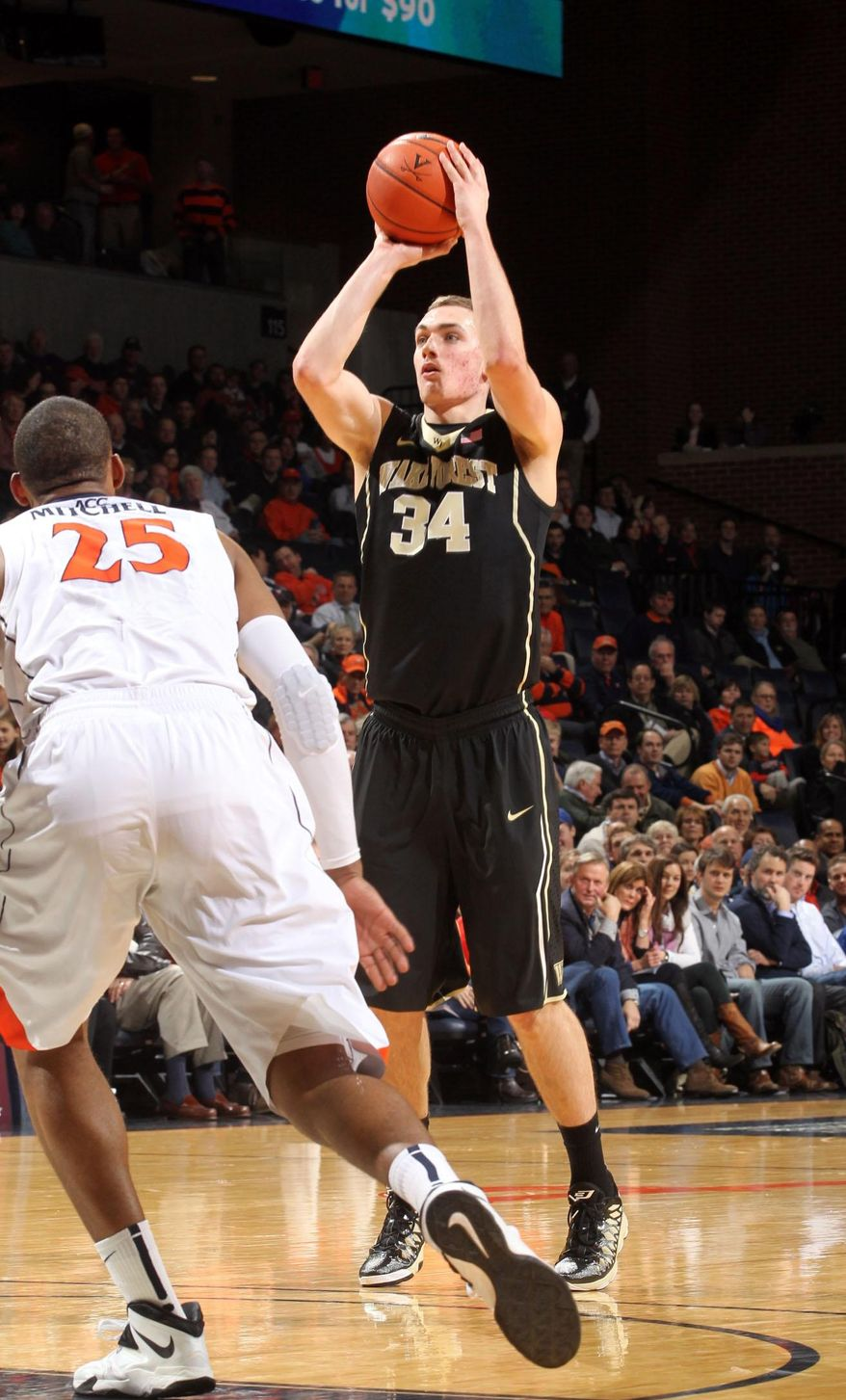 Wake Forest forward Tyler Cavanaugh (34) shoots over Virginia forward Akil Mitchell (25) during the first half of an NCAA college basketball game Wednesday, Jan. 8, 2014, in Charlottesville, Va. (AP Photo/Andrew Shurtleff)