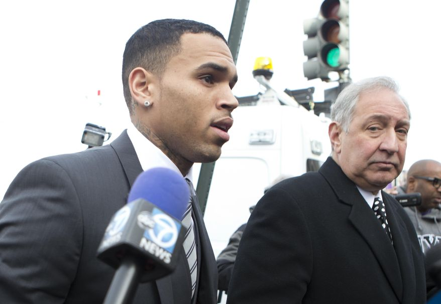 Singer Chris Brown, left, arrives at the District of Columbia Superior Court in Washington, Wednesday, Jan. 8, 2014, with his lawyer, for a status hearing in a case in which he's accused of hitting a man outside a Washington hotel. The R&B singer was arrested in October after a man said the singer hit him outside the W Hotel. Brown and his bodyguard each face a misdemeanor assault charge.    (AP Photo/Manuel Balce Ceneta)
