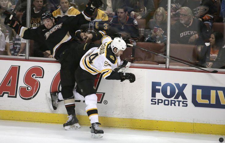 Boston Bruins defenseman Adam McQuaid, right, checks Anaheim Ducks left wing Patrick Maroon during the first period of an NHL hockey game in Anaheim, Calif., Tuesday, Jan. 7, 2014. (AP Photo/Chris Carlson)
