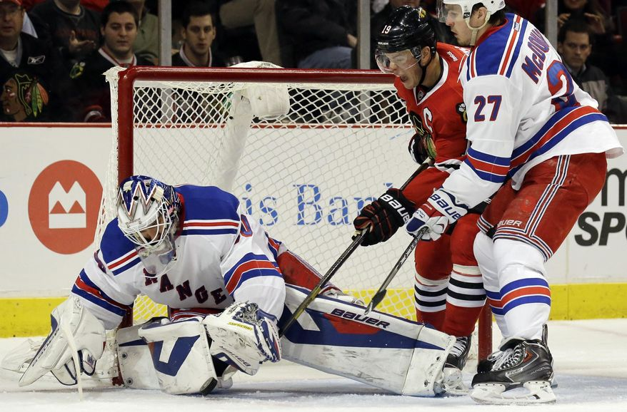 New York Rangers goalie Henrik Lundqvist (30), left, saves a shot by Chicago Blackhawks' Jonathan Toews (19) as Rangers' Ryan McDonagh (27) looks on during the second period of an NHL hockey game in Chicago, Wednesday, Jan. 8, 2014. (AP Photo/Nam Y. Huh)