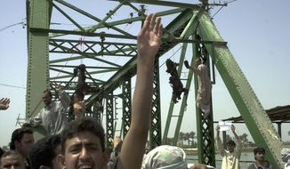 FILE - In this Wednesday, March 31, 2004 file photo, people chant anti-American slogans as charred bodies hang from a bridge over the Euphrates River in Fallujah, Iraq, west of Baghdad. Enraged Iraqis in this hotbed of anti-Americanism killed four foreigners Wednesday, and took the charred bodies from a burning SUV, dragged them through the streets, and hung them from the bridge. In 2014, the city's fall to al-Qaida-linked forces has touched a nerve for the service members who fought and bled there. (AP Photo/Khalid Mohammed)