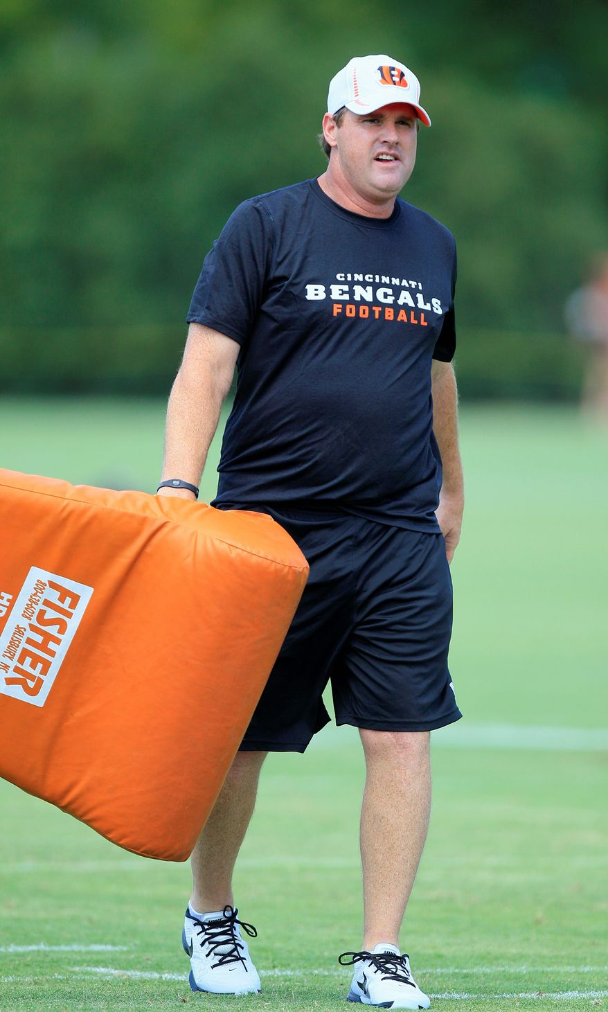 Cincinnati Bengals offensive coordinator Jay Gruden carries a pad during the NFL football team's first practice at training camp, Friday, July 27, 2012, in Cincinnati. (AP Photo/Al Behrman)
