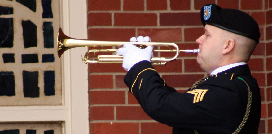Sgt. Mark Koehl plays taps outside a memorial service Thursday, January 9, 2014, at Fort Riley, Kan. Soldiers and families paid their respects to five soldiers who were killed in a Black Hawk helicopter crash in December in Afghanistan. (AP Photo/John Milburn)