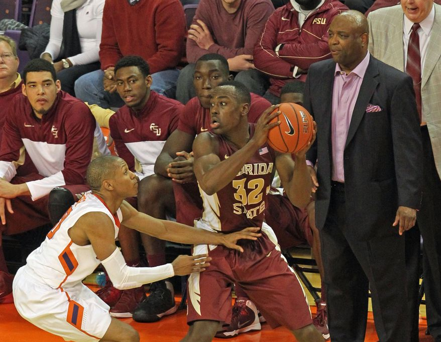 Florida State coach Leonard Hamilton, right, watches as Montay Brandon (32) protects the ball from Clemson defender Jordan Roper during the second half of an NCAA college basketball game at Littlejohn Coliseum in Clemson, S.C., on Thursday, Jan. 9, 2014. (AP Photo/Anderson Independent-Mail, Mark Crammer) GREENVILLE NEWS OUT   SENECA JOURNAL OUT