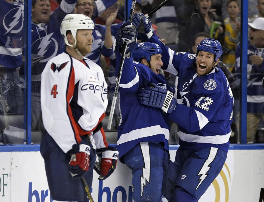 Tampa Bay Lightning right wing B.J. Crombeen, center, celebrates with teammate Ryan Malone, right, after scoring past the Washington Capitals, including defenseman John Erskine, left, during the second period of an NHL hockey game Thursday, Jan. 9, 2014, in Tampa, Fla. (AP Photo/Chris O'Meara)