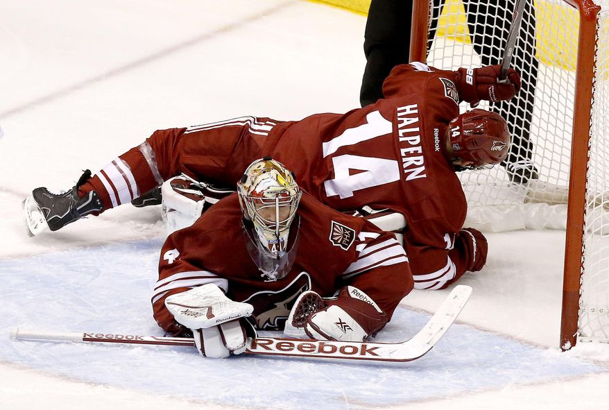 Phoenix Coyotes' Jeff Halpern (14) falls over goalie Mike Smith during the second period in an NHL hockey game against the Minnesota Wild Thursday, Jan. 9, 2014, in Glendale, Ariz. (AP Photo/Ross D. Franklin)