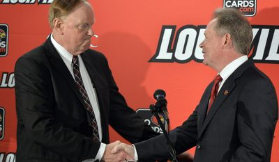 University of Louisville President Dr. James R. Ramsey, left, greets Bobby Petrino following he announcement of his hiring as the university's new NCAA college football coach Thursday, Jan. 9, 2014, at Papa John's Cardinal Stadium in Louisville, Ky. (AP Photo/Timothy D. Easley)