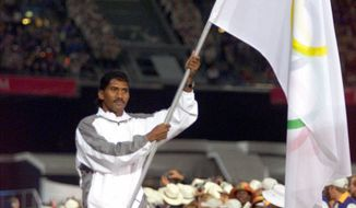 **FILE** Olympic athlete Victor Ramos carries the flag representing Individual Olympic Athletes onto the field during the opening ceremony for the Summer Olympics Friday, Sept. 15, 2000, at Olympic Stadium in Sydney. Ramos, a boxer, fled his homeland of East Timor following the 1999 violence. (AP Photo/David Guttenfelder)