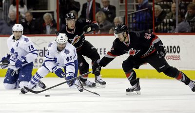 Carolina Hurricanes' Brett Sutter (42) and Alexander Semin, rear, of Russia, chase the puck against Toronto Maple Leafs' Nazem Kadri (43) and Joffrey Lupul (19) during the first period of an NHL hockey game in Raleigh, N.C., Thursday, Jan. 9, 2014. (AP Photo/Gerry Broome)
