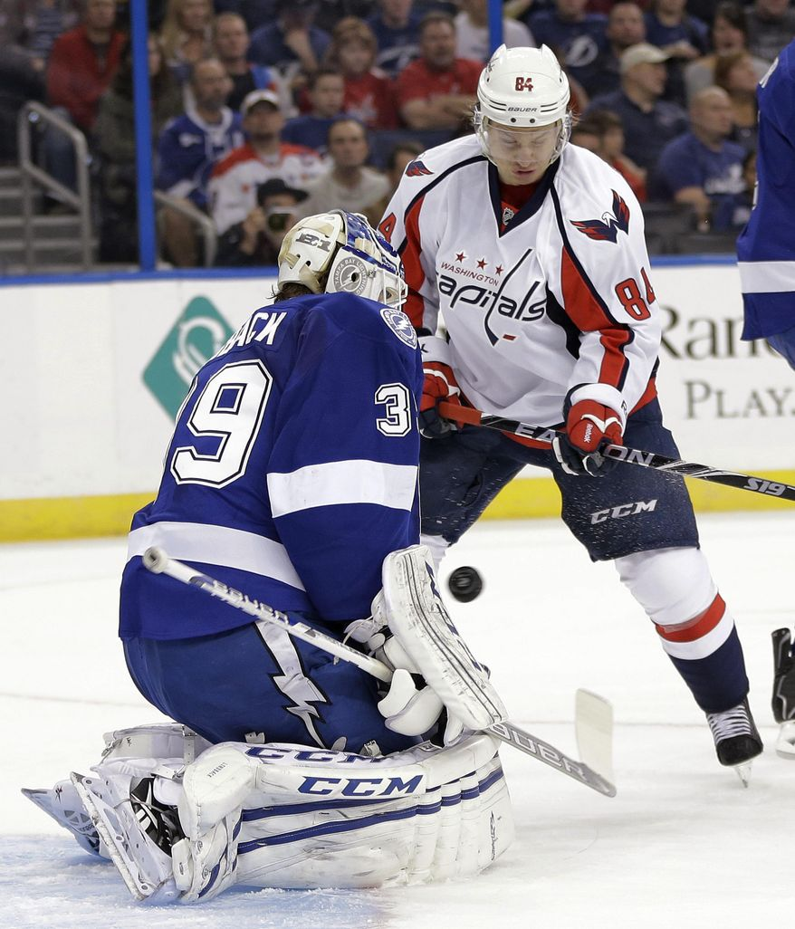 Washington Capitals center Mikhail Grabovski (84) deflects the puck past Tampa Bay Lightning goalie Anders Lindback (39) for a goal during the first period of an NHL hockey game Thursday, Jan. 9, 2014, in Tampa, Fla. (AP Photo/Chris O'Meara)