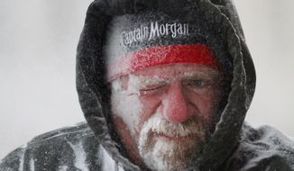 ** FILE ** In this Sunday, Jan. 5, 2014, file photo, Allan Umscheid, owner of Yards By Al, feels the bitter wind and catches drifting snow on his face as he runs a snowblower in Lawrence, Kan. The deep freeze that gripped much of the nation this week wasn't unprecedented, but with global warming we're getting far fewer bitter cold spells, and many of us have forgotten how frigid winter used to be. (AP Photo/The Journal-World, Mike Yoder, File)