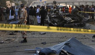 ** FILE ** Police cordon off the area of bombing in Karachi, Pakistan, Thursday, Jan. 9, 2014. (AP Photo/Shakil Adil)