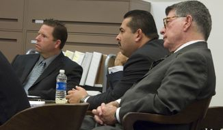 Former Fullerton police officers Jay Cicinelli, left, and Manuel Ramos listen with Ramos' defense attorney, John D. Barnett, right, as Orange County district attorney Tony Rackauckas delivers his rebuttal closing argument in the case against them stemming from the death of Kelly Thomas, a homeless man, who died after a violent 2011 confrontation with the [then] officers, Thursday, Jan. 9, 2014 in Santa Ana, Calf. The jury got the case Thursday after closing arguments ended in the five-week trial. (AP Photo/The Orange County Register, Joshua Sudock, Pool)