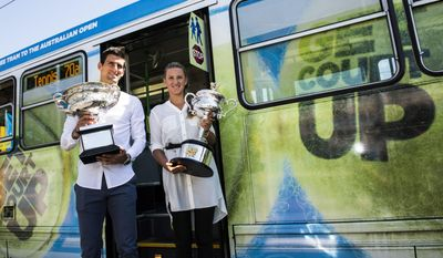 In this photo released by Tennis Australia, defending champions Serbia's Novak Djokovic and Victoria Azarenk of Belarus pose with their trophies beside a Melbourne tram prior to the official draw at the Australian Open tennis championship in Melbourne, Australia, Friday, Jan. 10, 2014. (AP Photo/Tennis Australia,Ben Solomon)