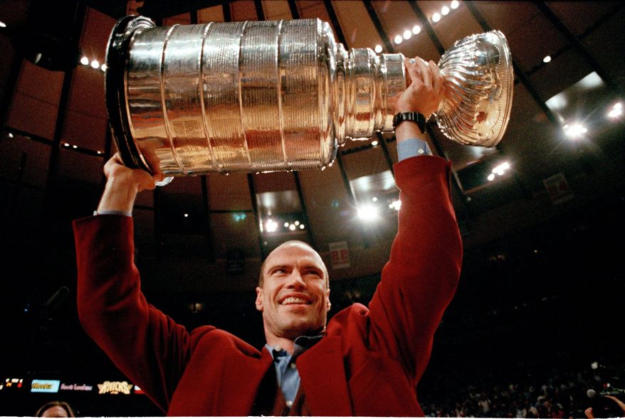 FILE - In this June 15, 1994 file photo, New York Rangers captain Mark Messier holds the Stanley Cup trophy overhead during half time of game four of the NBA finals at New York's Madison Square Garden in New York.  It has taken nearly 20 years for Mark Messier's nephew to get back in action at Madison Square Garden. Back then, as an infant, he sat in the Stanley Cup as the New York Rangers celebrated their first NHL championship in 54 years.  (AP Photo/Amy Sancetta, File)