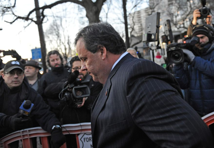 """New Jersey Gov. Chris Christie walks past reporters as he leaves City Hall Thursday, Jan. 9, 2014, in Fort Lee, N.J. Christie traveled to Fort Lee to apologize in person to Mayor Mark Sokolich. Moving quickly to contain a widening political scandal, Gov. Chris Christie fired one of his top aides Thursday and apologized repeatedly for the """"abject stupidity"""" of his staff, insisting he had no idea anyone around him had engineered traffic jams to get even with a Democratic mayor. (AP Photo/Louis Lanzano)"""