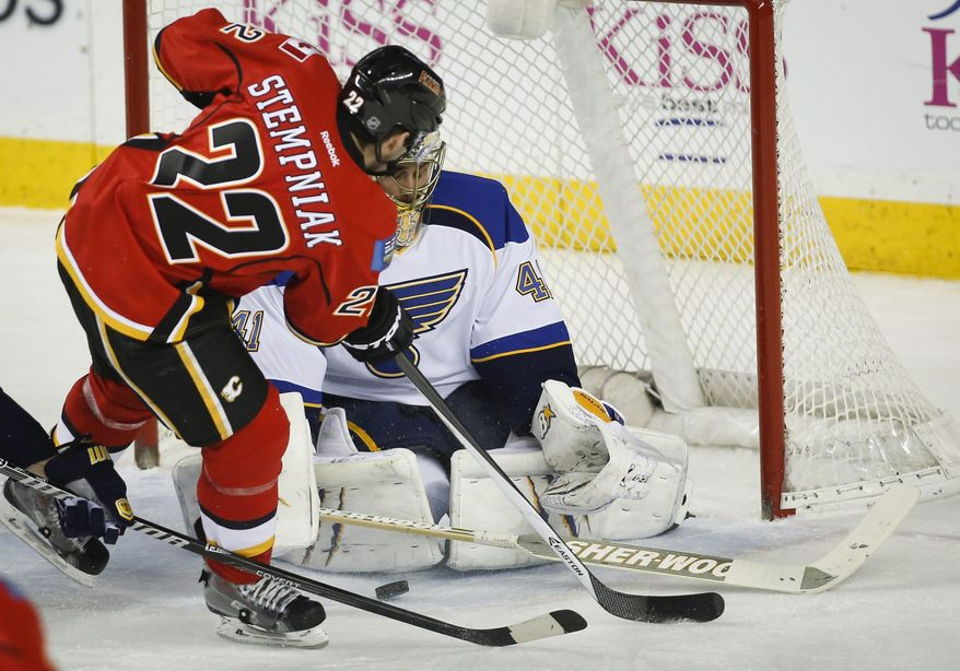 St. Louis Blues goalie Jaroslav Halak, right, from Slovakia, stops a shot from Calgary Flames' Lee Stempniak during second-period NHL hockey game action against the Calgary Flames in Calgary, Alberta, Thursday, Jan. 9, 2014. (AP Photo/The Canadian Press, Jeff McIntosh)