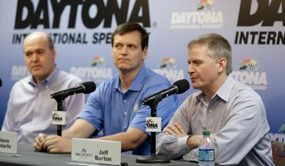 NASCAR driver Jeff Burton, right, speaks at a news conference with crew chief Steve Latarte, center, and Sam Flood, left,  Executive Producer at NBC Sports during Sprint Cup auto racing testing at Daytona International Speedway in Daytona Beach, Fla., Friday, Jan. 10, 2014. Latarte and Burton will join NBC Sports in 2015.(AP Photo/John Raoux)