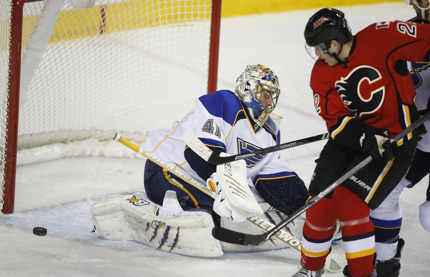 St. Louis Blues' goalie Jaroslav Halak, left, from Slovakia, looks for the puck as Calgary Flames' Lee Stempniak chases it during first-period NHL hockey game action against the Calgary Flames in Calgary, Alberta, Thursday, Jan. 9, 2014. (AP Photo/The Canadian Press, Jeff McIntosh)