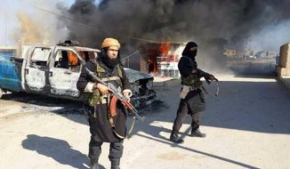This undated image posted on a militant website on Jan. 4, 2014, which is consistent with other AP reporting, shows Shakir Waheib, a senior member of the al-Qaida-linked Islamic State of Iraq and the Levant (ISIL), left, next to a burning police vehicle in Iraq's Anbar Province. With al-Qaida linked fighters and allied tribal gunmen camped on the outskirts, a tentative calm took hold over Fallujah on Friday, Jan. 10, 2014 and residents started to return to the besieged city west of Baghdad. Government forces were stationed nearby as sporadic street fighting breaks out in other cities. The picture painted by residents, officials and international groups suggests that both the militants and government forces are preparing for a long standoff with civilians caught in the middle.(AP Photo via militant website)