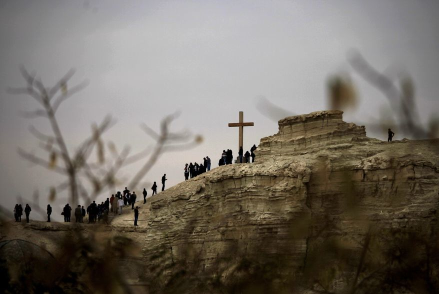 Christian pilgrims from around the world climb a small mountain near the Jordan River baptism site to take photos with a giant wooden cross, in South Shuna, Jordan Valley, Friday, Jan. 10, 2014. Thousands of pilgrims flock to the annual ceremony from both Jordanian and Israeli sides for the blessing of the waters at the baptism site where it is believed Jesus Christ was baptized. (AP Photo/Mohammad Hannon)