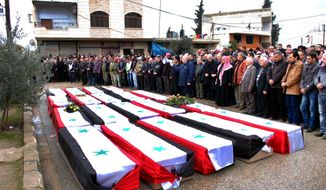 In this photo released by the Syrian official news agency SANA, Syrian citizens pray over the coffins wrapped by Syrian flags for the victims who were killed Thursday by a car bomb, during their funeral processions, at al-Kaffat village in the central Hama province, Syria, Friday, Jan. 10, 2014. Rebel-on-rebel fighting between an al-Qaida-linked group and an array of more moderate and ultraconservative Islamists has killed nearly 500 people over the past week in northern Syria, an activist group said Friday, in the most serious bout of violence among opponents of President Bashar Assad since the civil war began. (AP Photo/SANA)