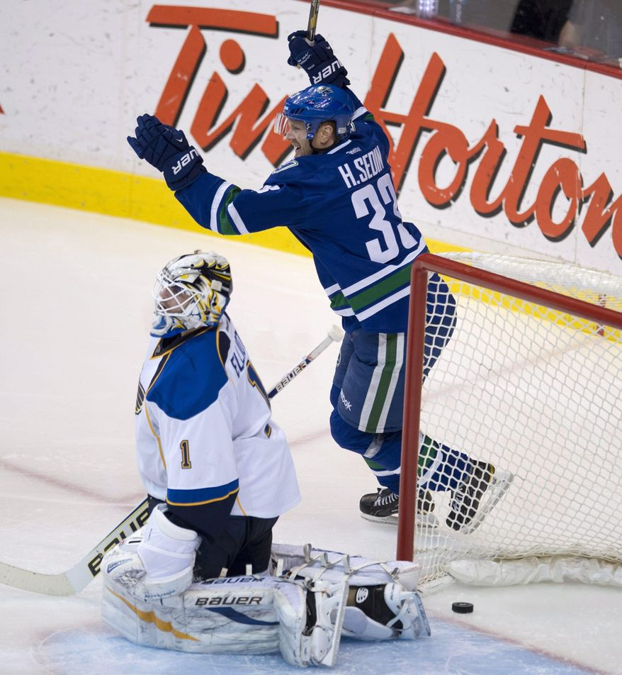 Vancouver Canucks center Henrik Sedin (33) celebrates Zac Dalpe's goal past St. Louis Blues goalie Brian Elliott during the second period of an NHL hockey game Friday, Jan. 10, 2014, in Vancouver, British Columbia. (AP Photo/The Canadian Press, Jonathan Hayward)
