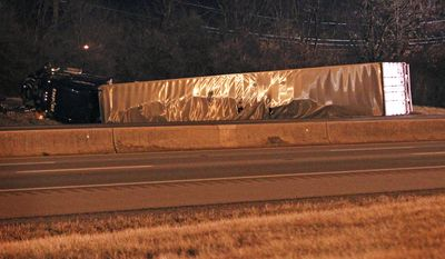 A tractor trailer lies on it's side after Lexington police closed Interstate 75 northbound because of the wreck at I-75 and North Broadway. Hazardous materials teams have been called to the scene as well on Friday Jan. 10, 2014 in Lexington, Ky.  (AP Photo/The Lexington Herald-Leader, Mark Cornelison)