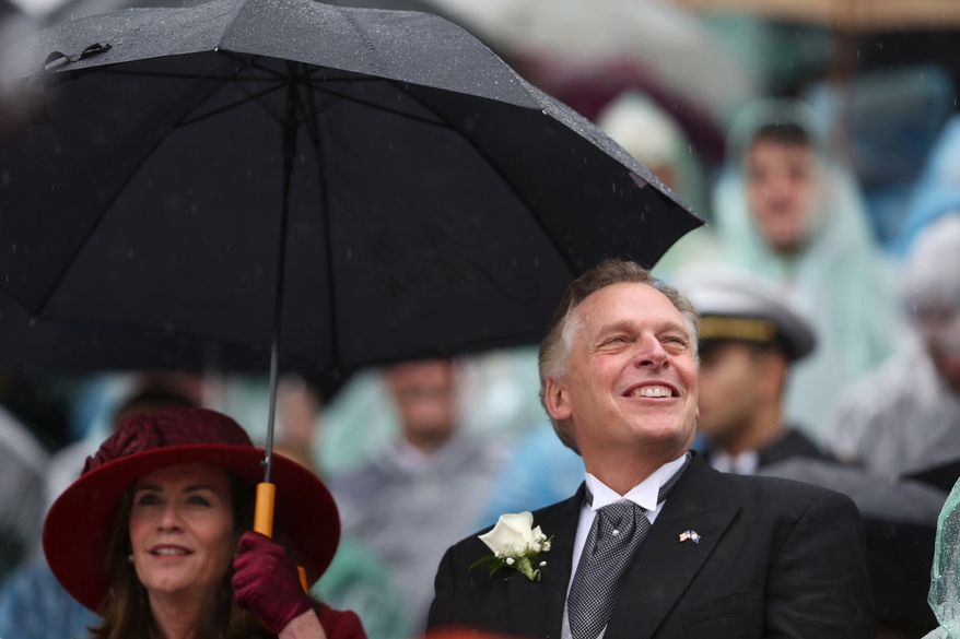 Terry McAuliffe and his wife Dorothy use an umbrella as McAuliffe is sworn in as Virginia's 72nd governor on Saturday, Jan. 11, 2014 at the state Capitol in Richmond, Va.  (AP Photo/The Virginian-Pilot, Steve Earley)