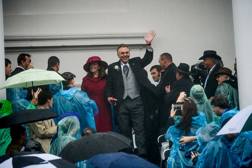 Terry McAuliffe waves as he and his wife Dorothy arrive before he is sworn in as the 72nd Governor of the Commonwealth of Virginia on a very rainy day in front of the Virginia State Capitol, Richmond, Va., Saturday, January 11, 2014. (Andrew Harnik/The Washington Times)