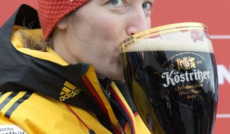 Winner Tatjana Huefner of Germany drinks beer on the podium after the women's luge World Cup  in Oberhof, Germany, Saturday, Jan. 11, 2014. (AP Photo/Jens Meyer)