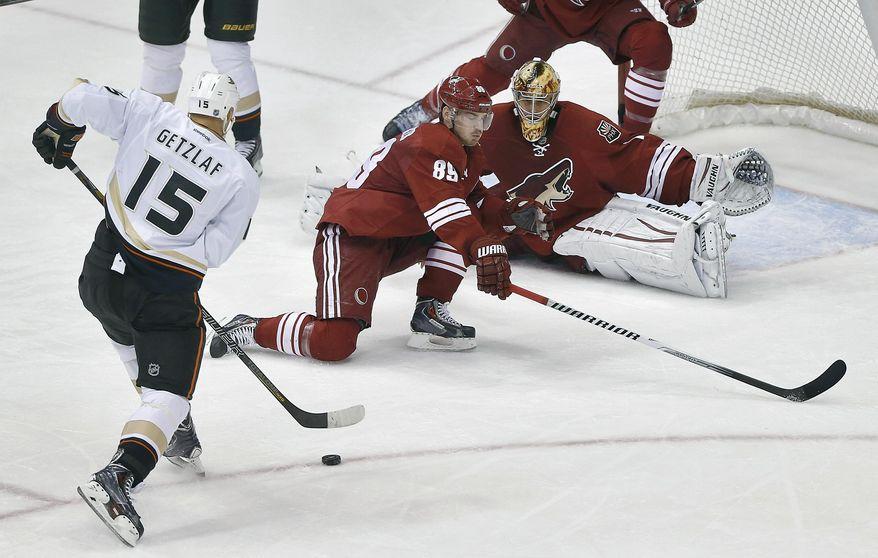 Anaheim Ducks' Ryan Getzlaf (15) scores against Phoenix Coyotes goalie Thomas Greiss and Mikkel Boedker (85) during the second period of an NHL hockey game, Saturday, Jan. 11, 2014, in Glendale, Ariz. (AP Photo/Matt York)