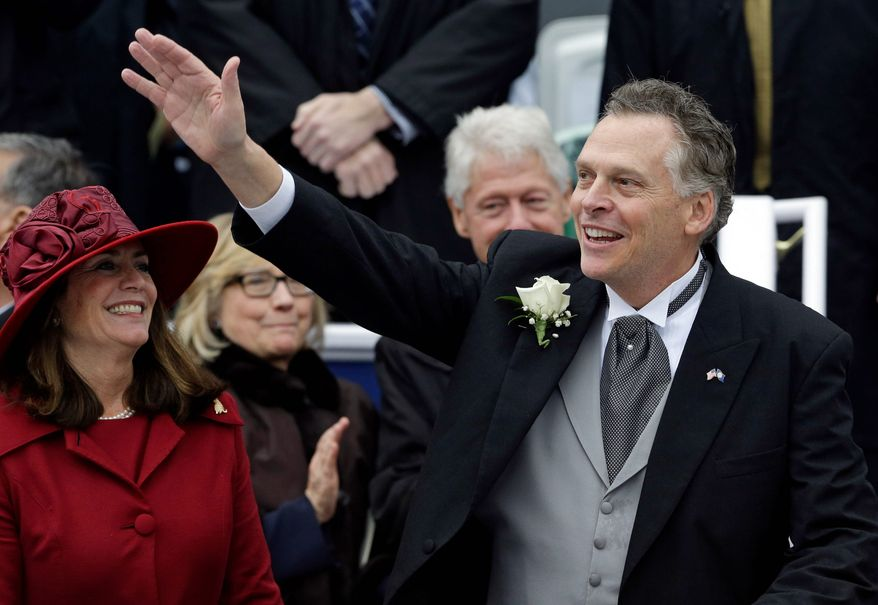 Virginia Gov. Terry McAuliffe waves to supporters alongside his wife, Dorothy, on Saturday during inaugural ceremonies at the Capitol in Richmond. Former U.S. Secretary of State Hillary Rodham Clinton and former President Bill Clinton look on in the background. (associated press)