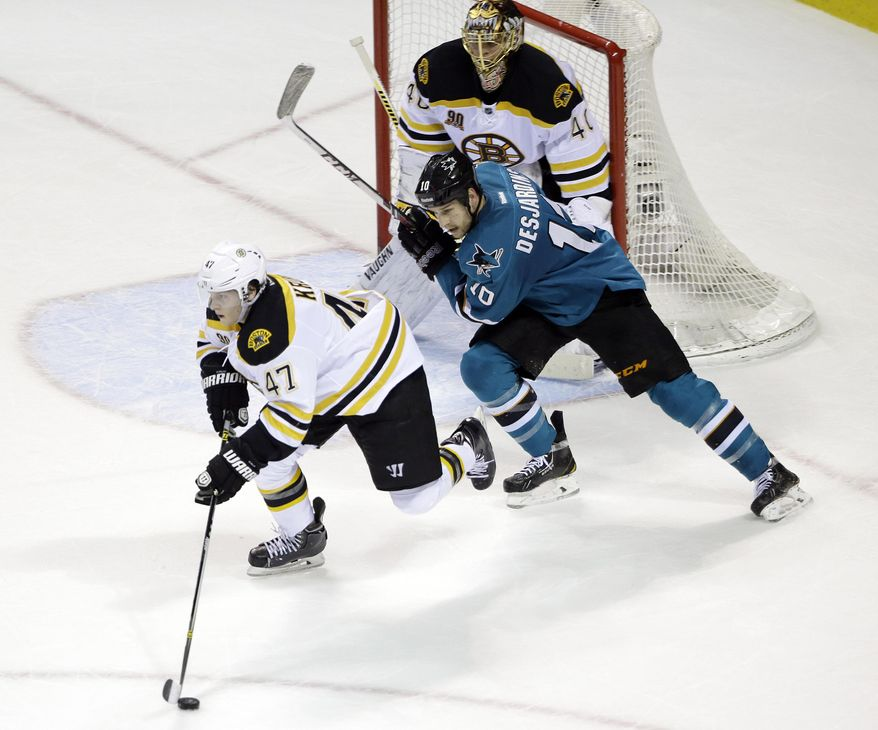 Boston Bruins' Torey Krug (47) skates with the puck as San Jose Sharks' Andrew Desjardins (10) chases during the first period of an NHL hockey game on Saturday, Jan. 11, 2014, in San Jose, Calif. (AP Photo/Marcio Jose Sanchez)