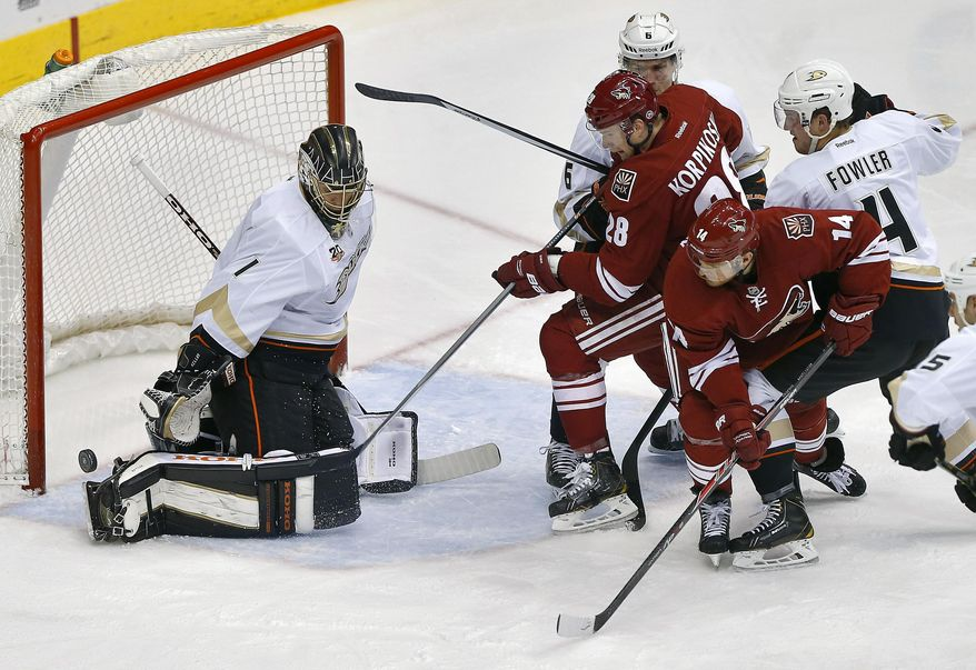 Anaheim Ducks goalie Jonas Hiller (1) deflects a shot as Phoenix Coyotes' Lauri Korpikoski (28) and Jeff Halpern (14) are defended by Ducks' Cam Fowler (4) and Ben Lovejoy (6) during the second period of an NHL hockey game, Saturday, Jan. 11, 2014, in Glendale, Ariz. (AP Photo/Matt York)