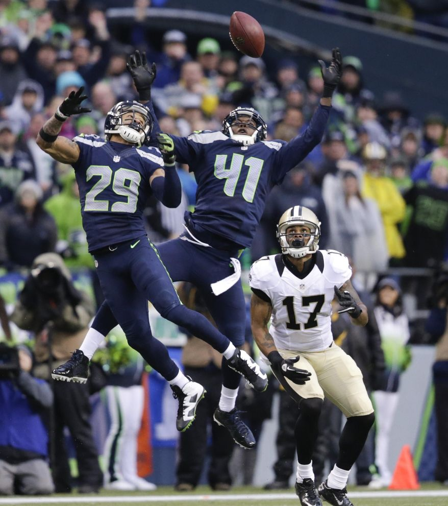 Seattle Seahawks free safety Earl Thomas (29) and cornerback Byron Maxwell (41) jump for a pass that was caught by New Orleans Saints wide receiver Robert Meachem (17) during the fourth quarter of an NFC divisional playoff NFL football game in Seattle, Saturday, Jan. 11, 2014. The Seahawks won 23-15. (AP Photo/John Froschauer)