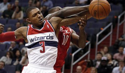 Washington Wizards guard Bradley Beal (3) and Houston Rockets forward Ronnie Brewer (10) go for a rebound in the first half of an NBA basketball game Saturday, Jan. 11, 2014, in Washington. (AP Photo/Alex Brandon)