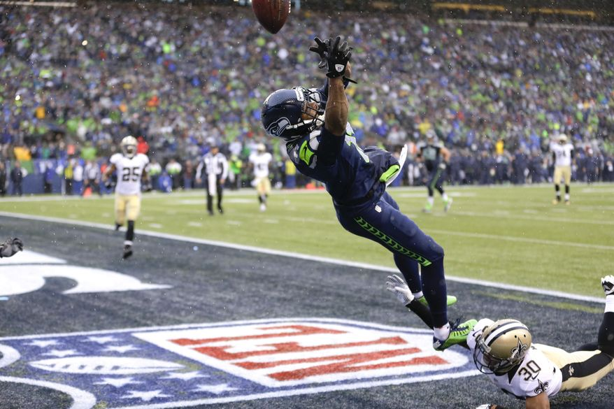 Seattle Seahawks wide receiver Percy Harvin, top, jumps for a pass, which he did not catch, over New Orleans Saints defensive back Trevin Wade during the second quarter of an NFC divisional playoff NFL football game in Seattle, Saturday, Jan. 11, 2014. Harvin was injured on the play. (AP Photo/Ted S. Warren)