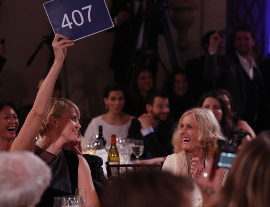 Charlize Theron, left, is seen bidding during the auction at the 3rd Annual Sean Penn & Friends HELP HAITI HOME Gala on Saturday, Jan. 11, 2014 at the Montage Hotel in Beverly Hills, Calif. (Photo by Colin Young-Wolff /Invision/AP)