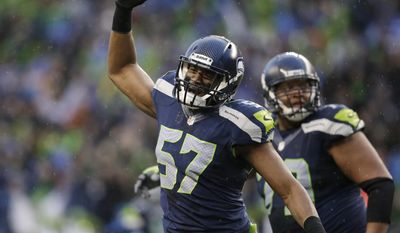 Seattle Seahawks linebacker Mike Morgan (57) celebrates after New Orleans Saints kicker Shayne Graham missed a 48-yard field goal during the fourth quarter of an NFC divisional playoff NFL football game in Seattle, Saturday, Jan. 11, 2014. (AP Photo/Elaine Thompson)